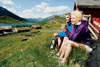 Valdres Natur- og Kulturparken. Foto: Fjell Norge / Terje Rakke . Par på tur sitter ved låve og ser på utsikt.